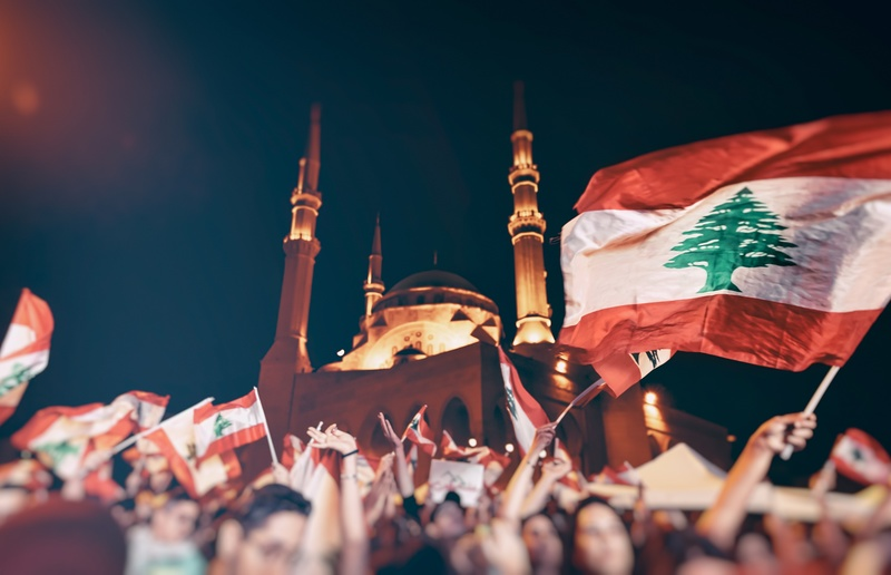Revolution in Lebanon, a crowd of people with Lebanese flags picket near the mosque and fight for their rights, power to people, togetherness, unity, and support of each other